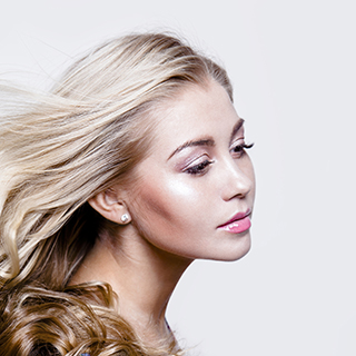 Attractive young blond woman with beautiful professional make-up. Fashion model studio portrait on light background.